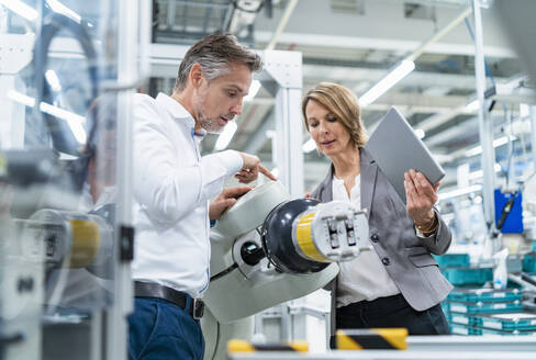 Businesswoman and man talking at assembly robot in a factory - DIGF07898