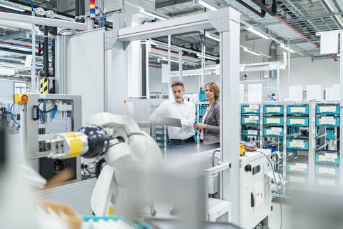 Businesswoman and manwith tablet talking in a modern factory - DIGF07901