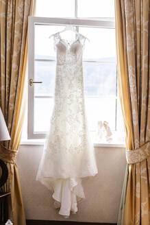 Ein Hochzeitskleid hängend vor einem Fenster, Österreich, Kärnten, Pörtschach - DAWF00900