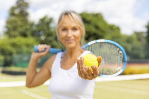 Smiling mature woman holding a tennis ball at tennis club - WPEF01764
