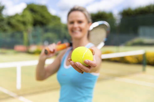 Smiling mature woman holding a tennis ball at tennis club - WPEF01767