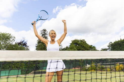 Happy female tennis player celebrating the victory on grass court - WPEF01770