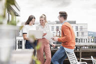 Casual business people with laptop meeting on roof terrace - UUF18546
