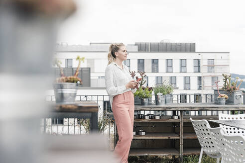 Casual businesswoman with cell phone on roof terrace - UUF18552