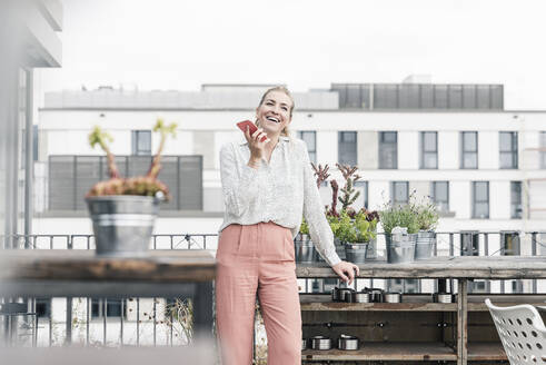 Happy casual businesswoman using cell phone on roof terrace - UUF18555