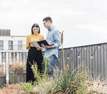 Casual businessman and woman with laptop and documents meeting on roof terrace - UUF18558