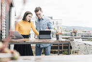 Casual businessman and woman with documents and tablet meeting on roof terrace - UUF18561