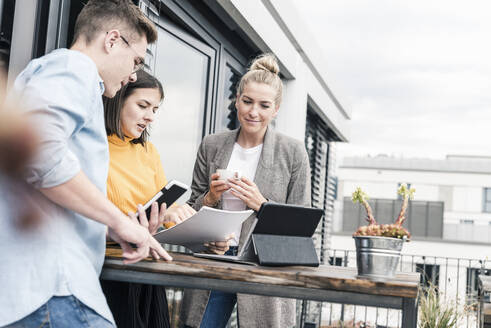 Casual business people meeting on roof terrace - UUF18564