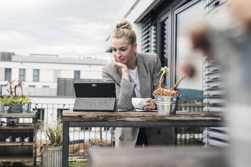 Businesswoman using tablet on roof terrace - UUF18567