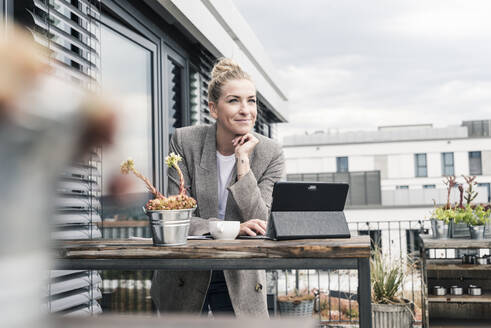 Businesswoman with tablet on roof terrace having a break - UUF18570