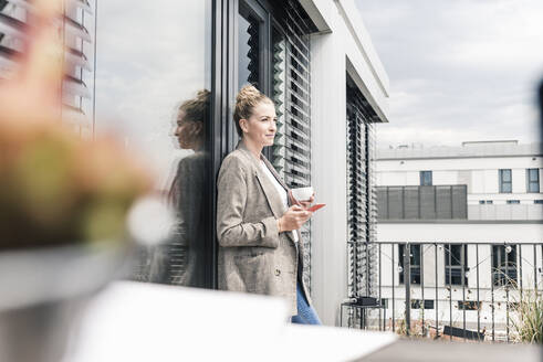 Businesswoman with cell phone and coffee cup standing on roof terrace - UUF18573