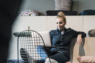 Smiling casual businesswoman using laptop in office lounge - UUF18582