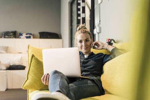 Casual businesswoman using laptop on couch in office lounge - UUF18588