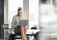 Businesswoman sitting on table in office using laptop - UUF18600