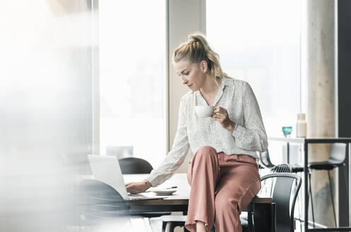 Businesswoman with cup of coffee sitting on table in office using laptop - UUF18606