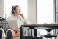 Smiling businesswoman sitting at table in office with laptop - UUF18612
