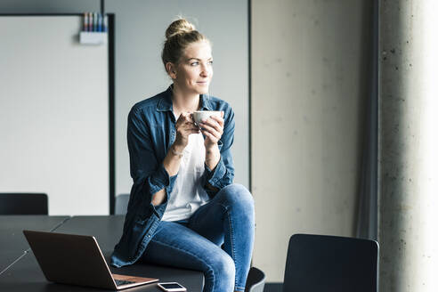 Smiling businesswoman sitting on table in office having a coffee break - UUF18618