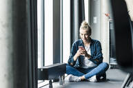 Businesswoman sitting on the floor in office using cell phone - UUF18621