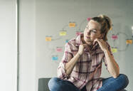 Casual businesswoman sitting on table in office with mind map in background - UUF18633