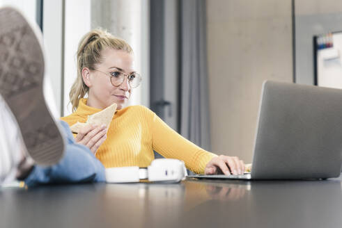 Casual businesswoman sitting at table in office using laptop and eating a sandwich - UUF18636
