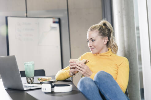 Casual businesswoman sitting at table in office looking at laptop and eating a sandwich - UUF18639