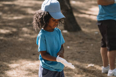 Little girl preparing to clean the forest - JCMF00103