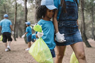 Woman and girl walking hand in hand collecting garbage in a park - JCMF00112