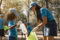Group of volunteers collecting garbage in a park - JCMF00115