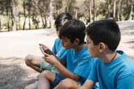 Three boys in blue t-shirts using smartphone - JCMF00118