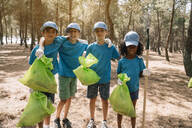 Group portrait of volunteering children collecting garbage in a park - JCMF00121