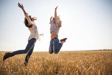 Caucasian women jumping for joy in rural field - BLEF13923