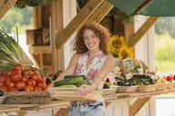 Caucasian woman holding produce at farmers market - BLEF14079