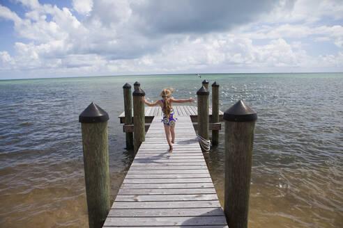 Caucasian girl walking on pier - BLEF14160