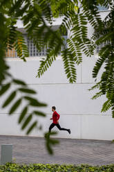 Young athlete doing intensive running training in the city - MAUF02728