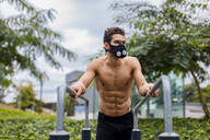 Athlete training on bars in the city, wearing breathing mask - MAUF02731