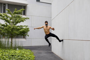 Athlete doing intense training with breathing mask, jumping against house wall - MAUF02734