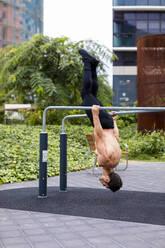 Athlete training on bars in the city, wearing breathing mask - MAUF02737