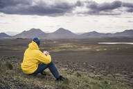 Man drinking coffee, looking at landscape in Iceland - UUF18655