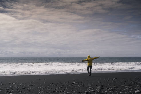 Mature man on a lava beach in Iceland, rear view - UUF18670