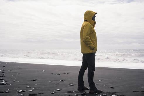 Mature man on a lava beach in Iceland, looking at the sea - UUF18673