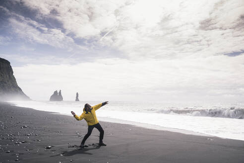 Mature man throwing a stone into the sea, on a lava beach in Iceland - UUF18676