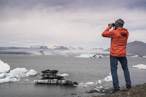 Mature man watching Vatnajokull glacier with binoculars, Iceland - UUF18712
