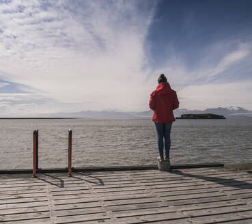 Young woman standig on a jetty, looking at the sea, South East Iceland - UUF18733