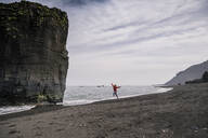 Woman on lava beach in South East Iceland, running and jumping for joy - UUF18739