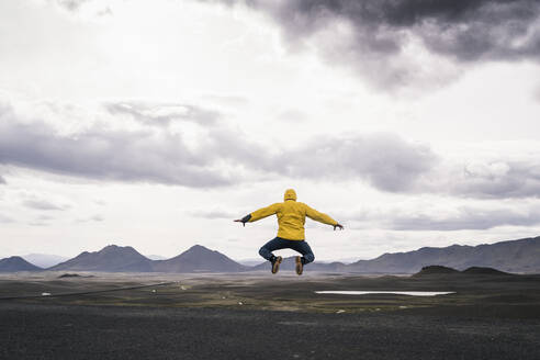 Mature man jumping for joy in the Highland Region, Iceland - UUF18748