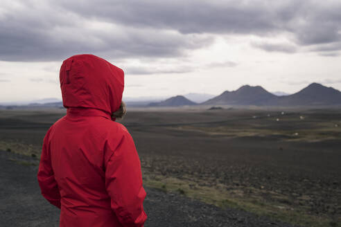 Young woman looking at highlands, Iceland - UUF18751