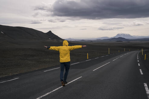 Man balancing on center line of empty road, Iceland - UUF18754