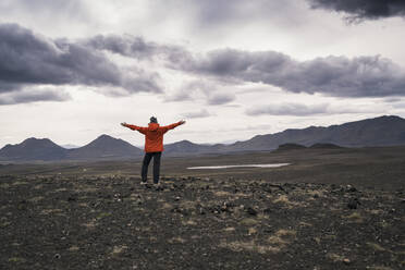 Young woman looking at view, with arms outstretched, Highland region, Iceland - UUF18763