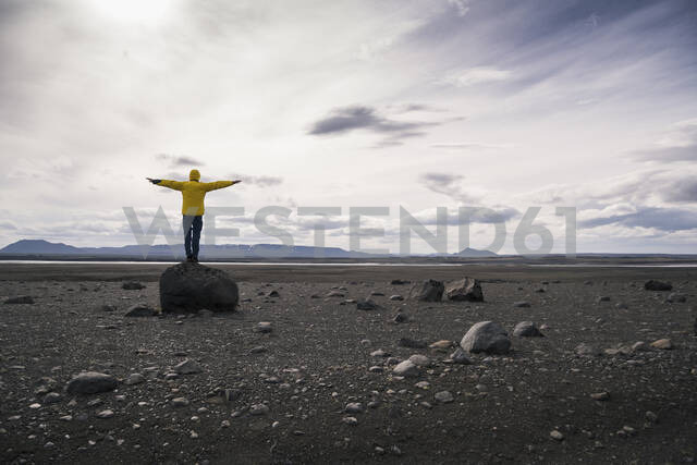 Mature man standing on a rock in the volcanic highlands of Iceland with arms out - UUF18769 - Uwe Umstätter/Westend61