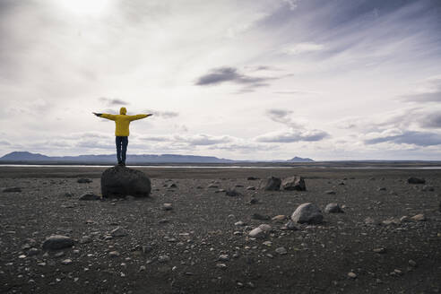 Mature man standing on a rock in the volcanic highlands of Iceland with arms out - UUF18769